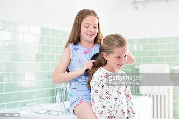 Big sister brushing little sisters hair