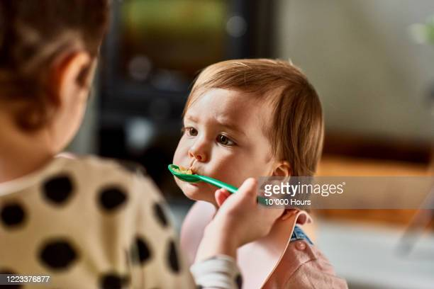 big sister feeding toddler - baby stock pictures, royalty-free photos & images