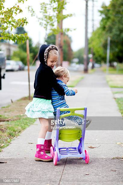 Big sister helps little brother into stroller