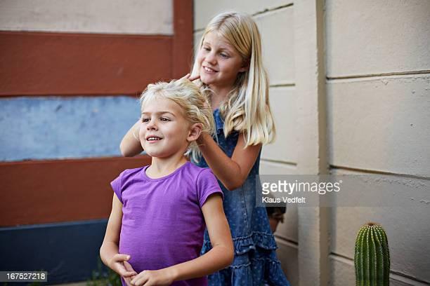 Big sister making ponytale on her little sister