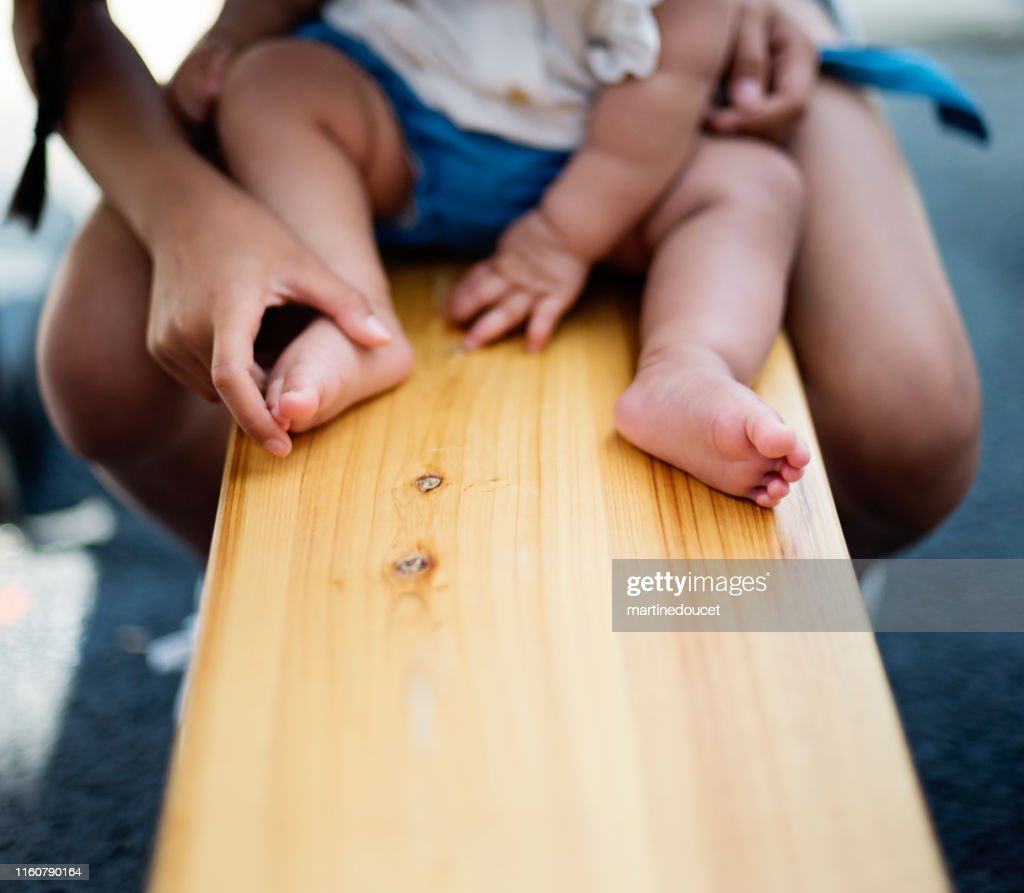 Big sister playing with baby's feet on bench. : Stock Photo