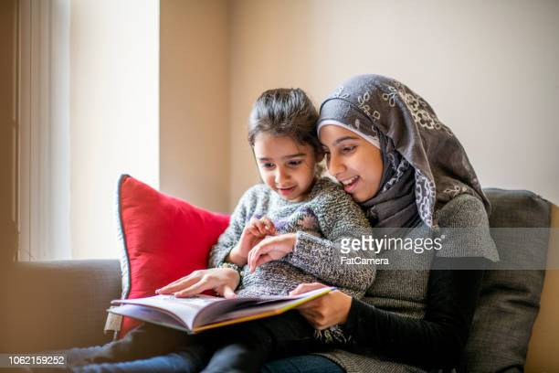 big sister reads stories to her little sister - reading stock pictures, royalty-free photos & images