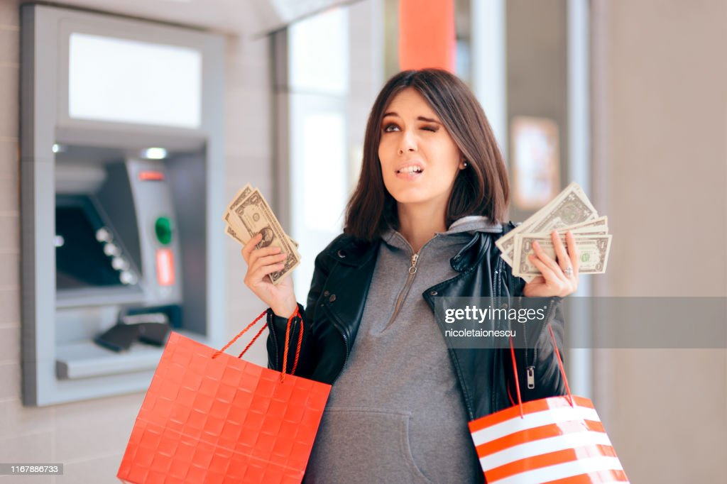 Big Spender Holding Money in front of the ATM : Stock Photo