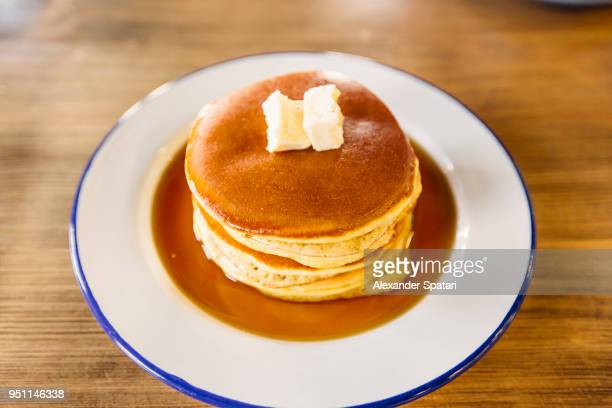 Big stack of American pancakes with butter and maple syrup on a plate