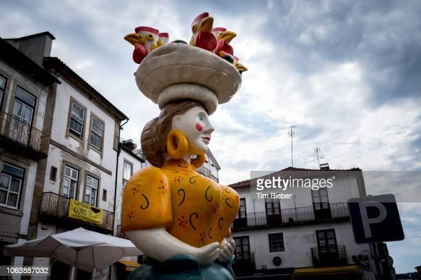 big statue of woman with basket of birds on her head. - galo de barcelos imagens e fotografias de stock