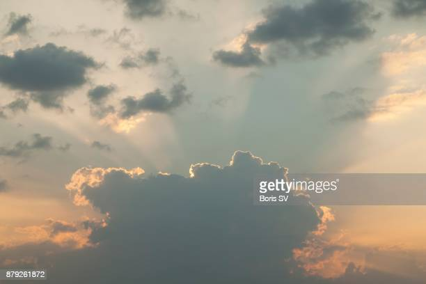 Big stratocumulus cloud covering sun with beams of light