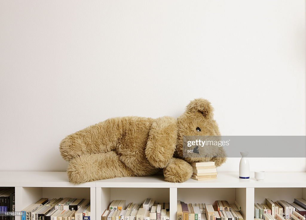 Big teddy bear lying on bookcase : Stock Photo