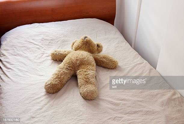Big teddy bear lying  on the bed