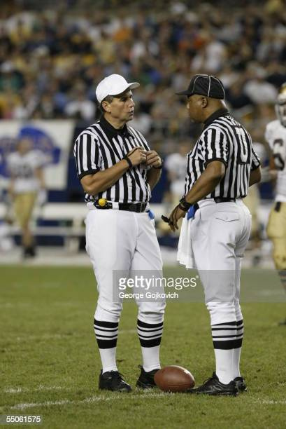 Big Ten officials, referee Dennis Lipski and umpire Carl Britt, talk during a game between the Notre Dame Fighting Irish and University of Pittsburgh...