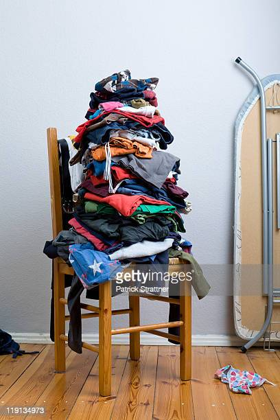 a big untidy stack of clean clothes waiting to be ironed - cadeira - fotografias e filmes do acervo