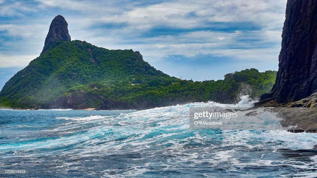 A big wave, in the background Cacimba do Padre Beach and Morro do Pico. : Stock Photo
