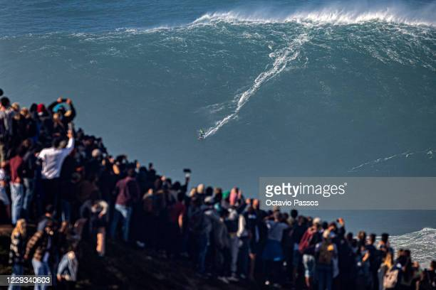 Big wave surfer Carlos Burle of Brazil rides a wave during a tow surfing session at Praia do Norte on October 29, 2020 in Nazare, Portugal.