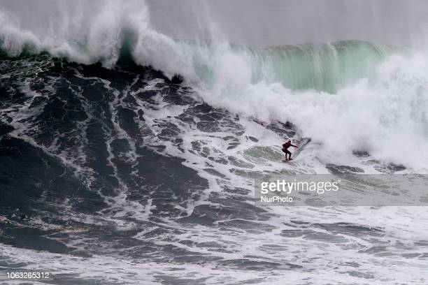Big wave surfer drops a wave during a tow-in surf session at Praia do Norte in Nazare, Portugal on November 18, 2018.