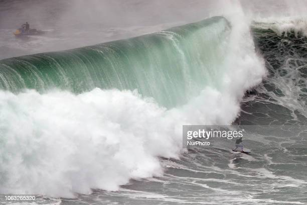 A big wave surfer drops a wave during a towin surf session at Praia do Norte in Nazare Portugal on November 18 2018