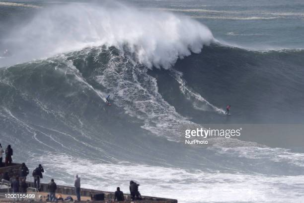 Big wave surfers Andrew Cotton of Great Britain and Lucas Chianca of Brazil drop a wave during the WSL Nazare Tow Surfing Challenge at Praia do Norte...