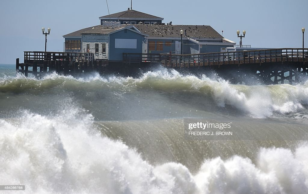 Big waves crash ashore and into the pier at Seal Beach, California on August 27, 2014, where some overnight flooding occurred as the surging ocean water resulting from Hurricane Marie almost reached beachfront homes. And as surfers prep for what could be some of the biggest swells of the year, county and city officials are using tractors to fill in sand berms along coastal beaches, in a hopeful effort to avoid any flooding or other damage resulting from Hurricane Marie. AFP PHOTO / Frederic J. BROWN