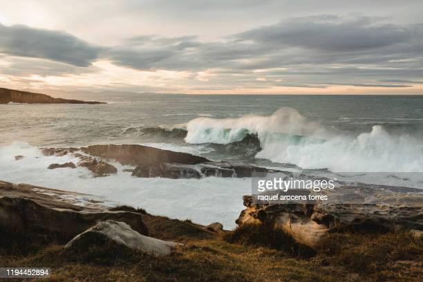 big waves in the sea during sunset with cloudy sky - オンダリビア ストックフォトと画像