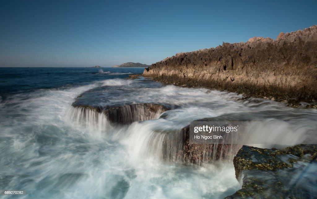 Big waves struck coral rock coast at HangRai Cave, Ninhthuan, Vietnam creating a waterfall in the ocean : Stock Photo