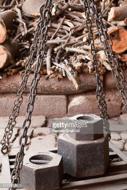 big weights used to weigh wood to be sold for the cremation funeral pyres on manikarnika ghat and harishchandra ghat in varanasi, india. - manikarnika ghat stock photos and pictures