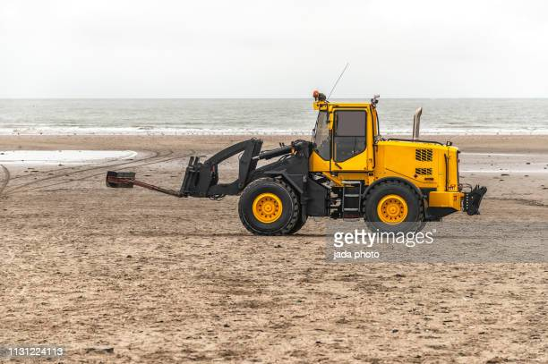 big yellow bulldozer with drives over the beach of ijmuiden netherlands - caterpillar stock pictures, royalty-free photos & images