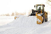 A big yellow snow plow cleaning a road