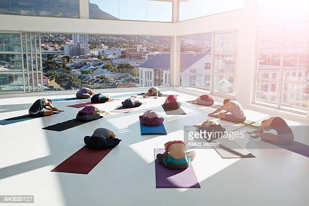 Big yoga class practicing in huge rooftop studio