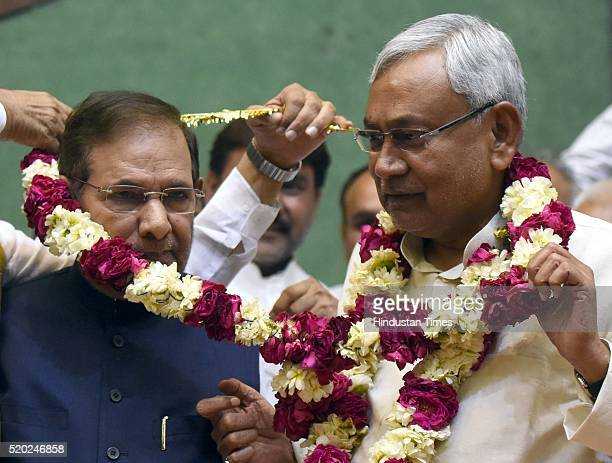 Bihar Chief Minister and newly elected JD National President Nitish Kumar being greeted by outgoing party President Sharad Yadav and National...