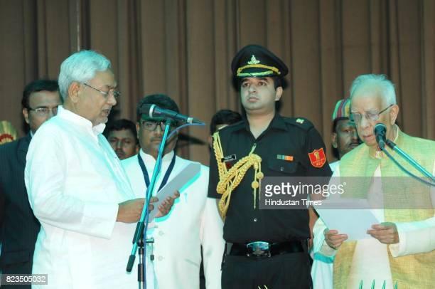 Bihar Governor Keshari Nath Tripathi administers oath to JD President Nitish Kumar as Bihar Chief Minister at Raj Bhawan on July 27 2017 in Patna...