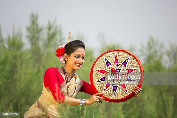 Bihu dancer holding a jaapi
