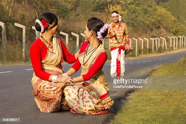 Bihu dancers squatting as Bihu man walks up