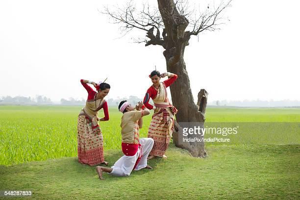 Bihu man playing on a pepa while Bihu women dance to his tune