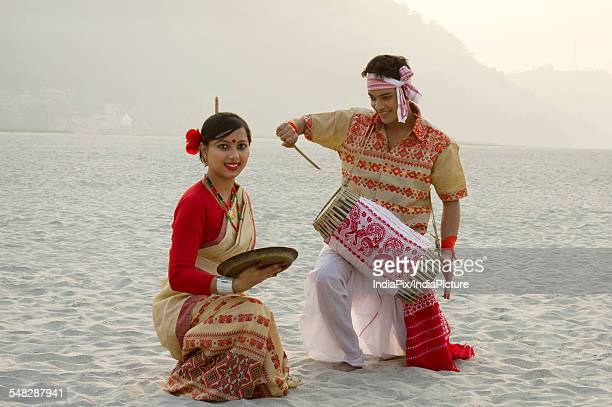 Bihu woman dancing with a brass plate as Bihu man plays on a dhol