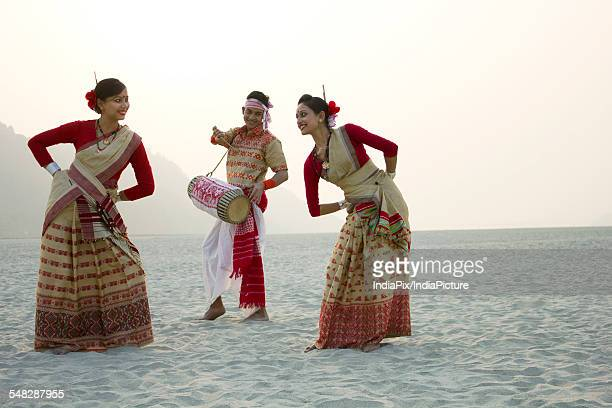 Bihu women dancing as Bihu man plays on a dhol