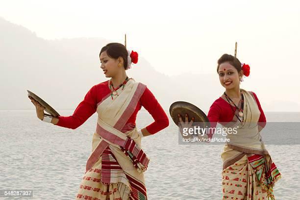 Bihu women dancing with brass plates