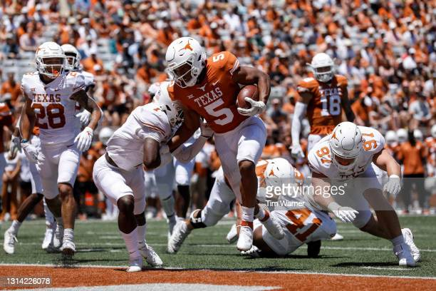 Bijan Robinson of the Texas Longhorns rushes for a touchdown while defended by Chris Adimora in the first half during the Texas Football Orange-White...