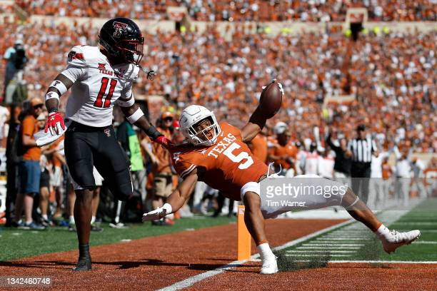 Bijan Robinson of the Texas Longhorns scores a receiving touchdown while defended by Eric Monroe of the Texas Tech Red Raiders in the first quarter...