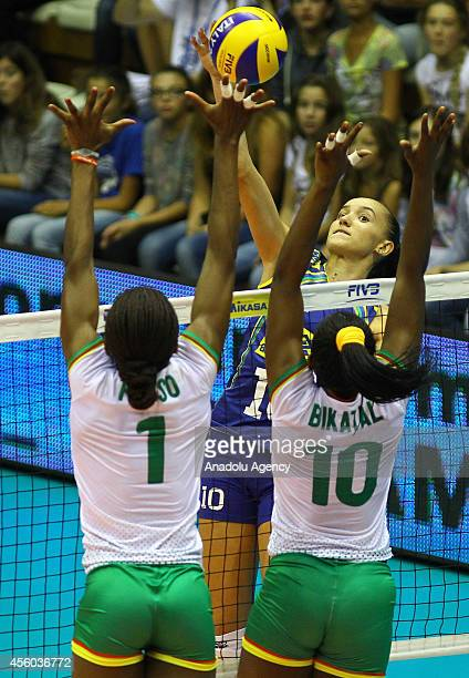 Bikatal and Fotso of Cameroon in action against Gabriela Guimaraes of Brazil during the 2014 FIVB Volleyball Women's World Championship Group B match...