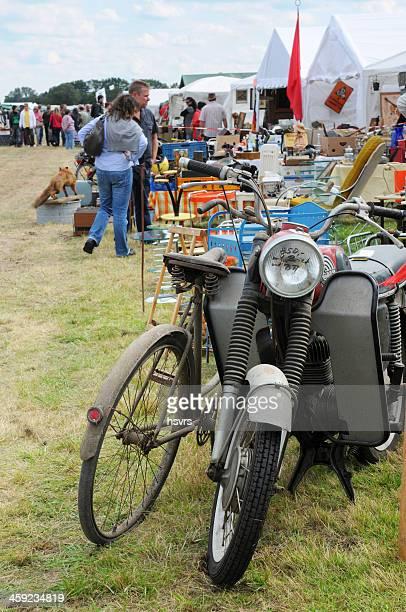 自転車とオートバイのフリーマーケットで、観光客が背景 - ガレージセール ストックフォトと画像