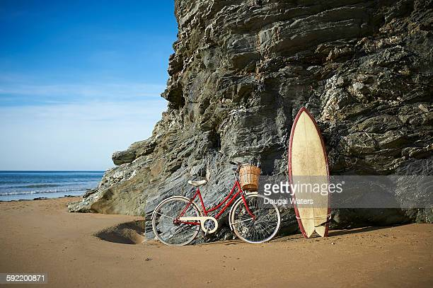 Bike and surf board leaning against rocks at beach