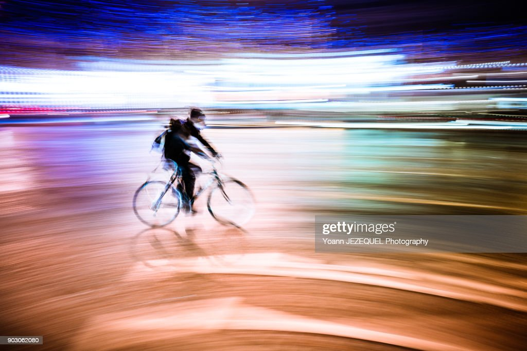 Motion shot of a bike on Champs Elysees. Man is wearing a pollution mask.