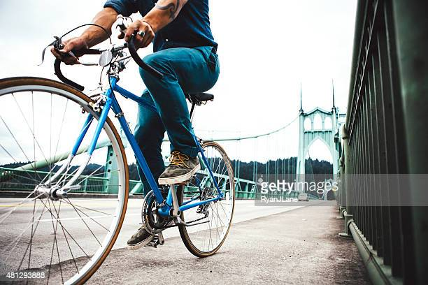 bike commuter in portland oregon on st johns bridge - willamette river stock photos and pictures