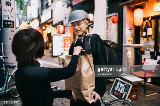 bike courier receiving a delivery - japan stock pictures, royalty-free photos & images