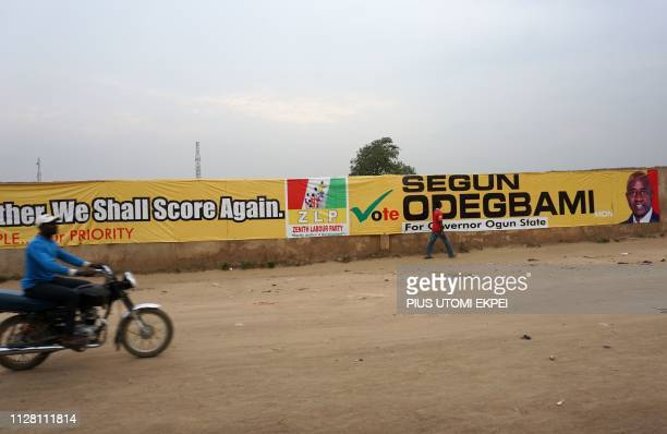 A bike drives past long campaign banner bearing photograph of former captain of Nigerian national football team the Super Eagles Segun Odegbami who...