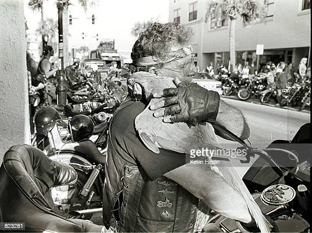 A bike hugs his pet parrot while sitting on his Harley Davidson motorcycle March 5 2000 during Daytona Beach Bike Week in Daytona Beach Florida The...