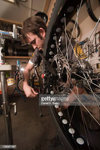bike mechanic, 27 years old, doing final assembly on a fat tire snow bike on a bike stand in the workshop at speedway cycles, anchorage, alaska, usa - 25 29 years stock pictures, royalty-free photos & images