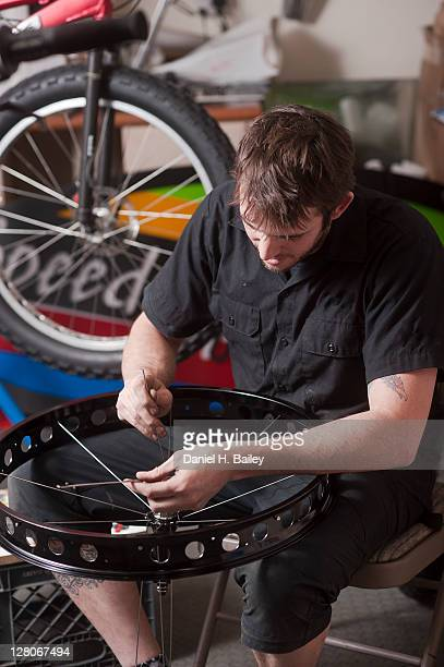 bike mechanic, 27 years old, lacing spokes up in a four inch wide wheel for a fat tire snow bike in the workshop at speedway cycles, anchorage, alaska, usa - 25 29 years stock pictures, royalty-free photos & images