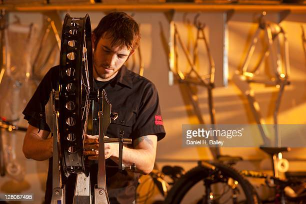 bike mechanic, 27 years old, truing spokes up in a four inch wide wheel for a fat tire snow bike in the workshop at speedway cycles, anchorage, alaska, usa - 25 29 years stock pictures, royalty-free photos & images