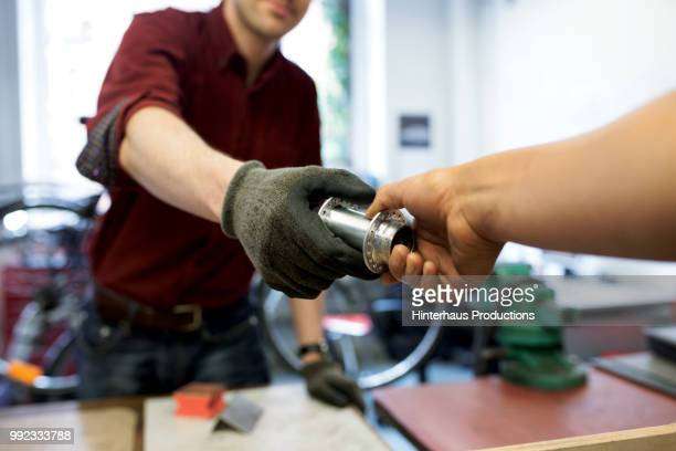 bike mechanic handing bicycle part to colleague - vehicle part stock pictures, royalty-free photos & images