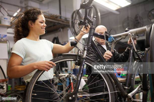 Bike Mechanic Working On Bicycle With Apprentice