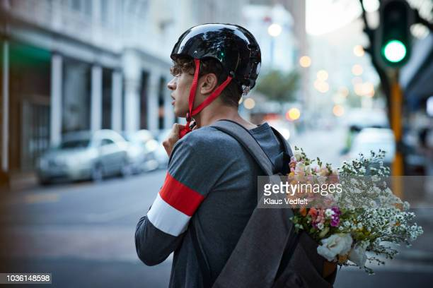 bike messenger carrying flowers in backpack - cycling helmet stock photos and pictures